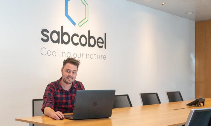 CEO of Sabcobel zit aan een tafel met laptop met het log van Sabcobel op de achtergrond.