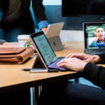 A group opf people around a desktop having a Teams meeting