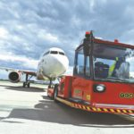 TCR voertuig versleept vliegtuig op tarmac.