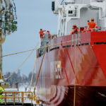 Ein großes rotes Schiff mit einigen Personen an Bord in der Werft