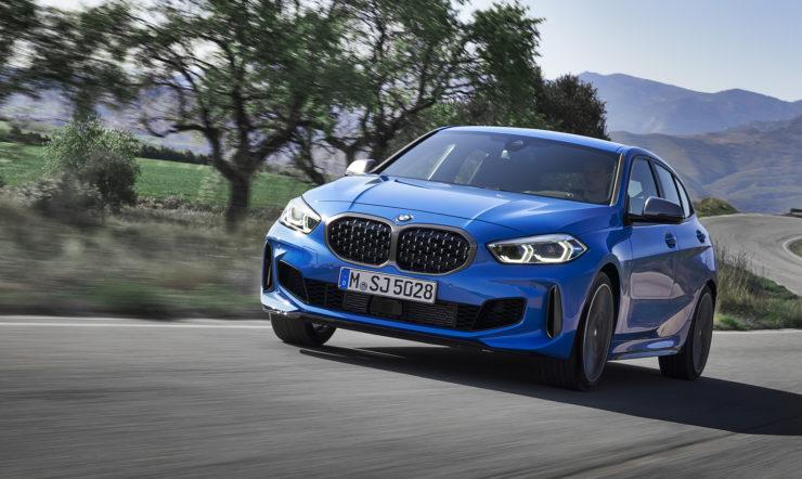 BMW bleue roulant sur une route dans un paysage montagneux.