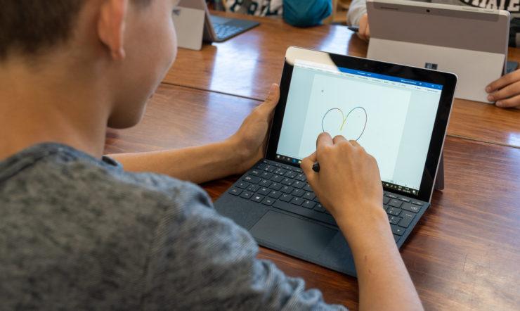 een man met behulp van een laptop computer zittend op de top van een tafel