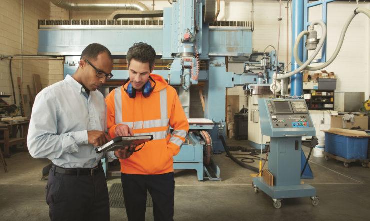 En mand på en fabrik kigger på en tablet