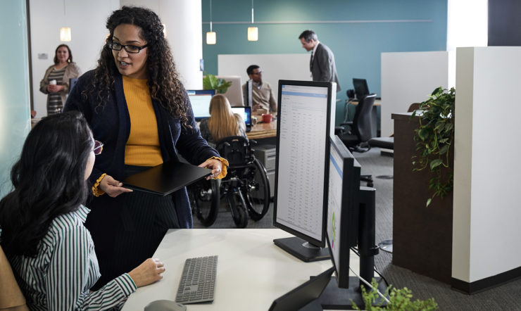 To personer, der sidder og står foran en computer