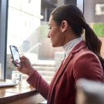 Eine Person, vor einem Fenster ein Telefon hält