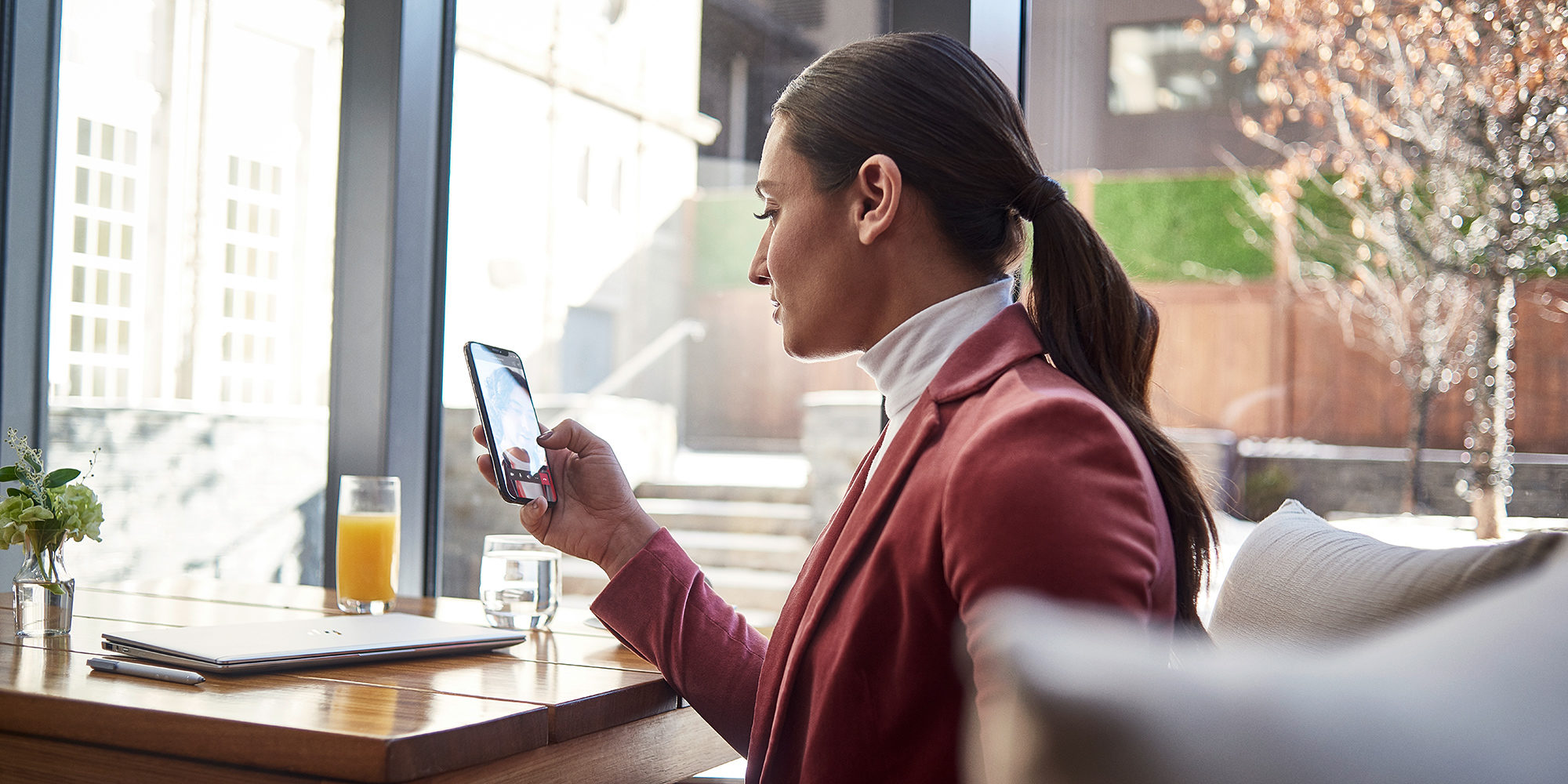 iemand die een telefoon vasthoudt voor een raam
