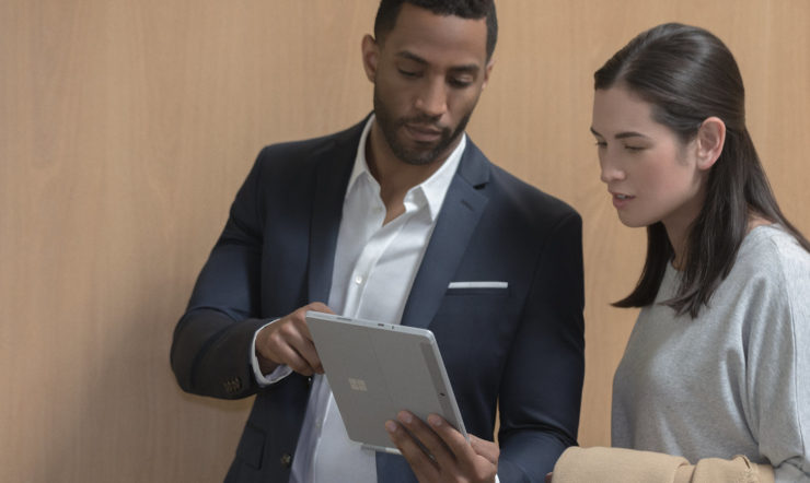 Two people inside using Surface Go in office