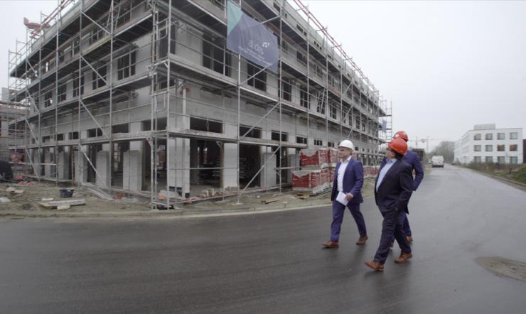 3 mannen die voorbij een bouwwerf wandelen.