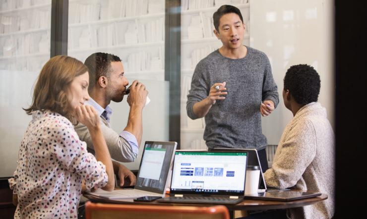 een groep mensen kijkt naar een laptop