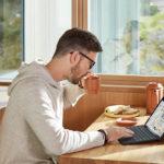 mies istuu pöydän ja edessä näpytellen tietokonetta