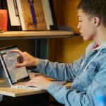en mand bruger en bærbar computer, mens har sidder på et bord
