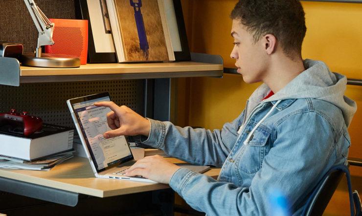 een man gebruikt een laptop op een bureau