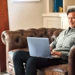 un hombre sentado en una sala de estar con una silla de cuero