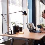 en person sidder ved et skrivebord med en bærbar computer på et bord