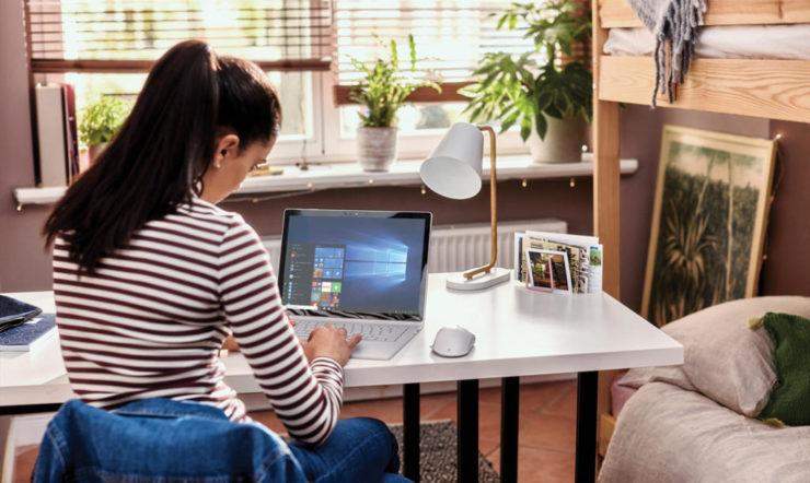 en person sitter vid ett bord och använder en bärbar dator
