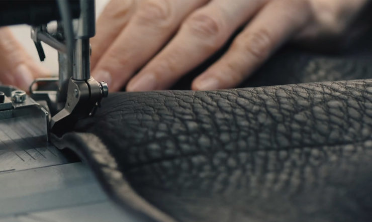 Primo piano di una mano che cuce un tessuto in pelle