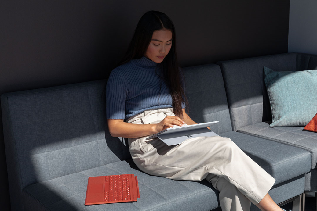 Contextual image of woman inside working on Surface Pro 7