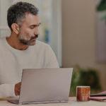 mies seisoo kannettavan tietokoneen edessä