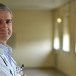 um médico de bata branca e a sorrir para a câmara