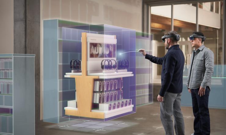 To menn står foran et digitalt stativ i en butikk med HoloLens. Den ene samhandler med det