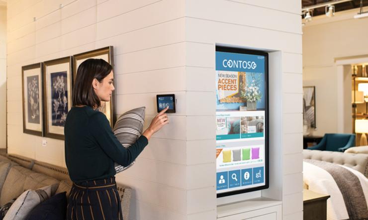 Une femme se trouvant dans un magasin de meubles utilise une tablette placée sur un mur tout en tenant un coussin