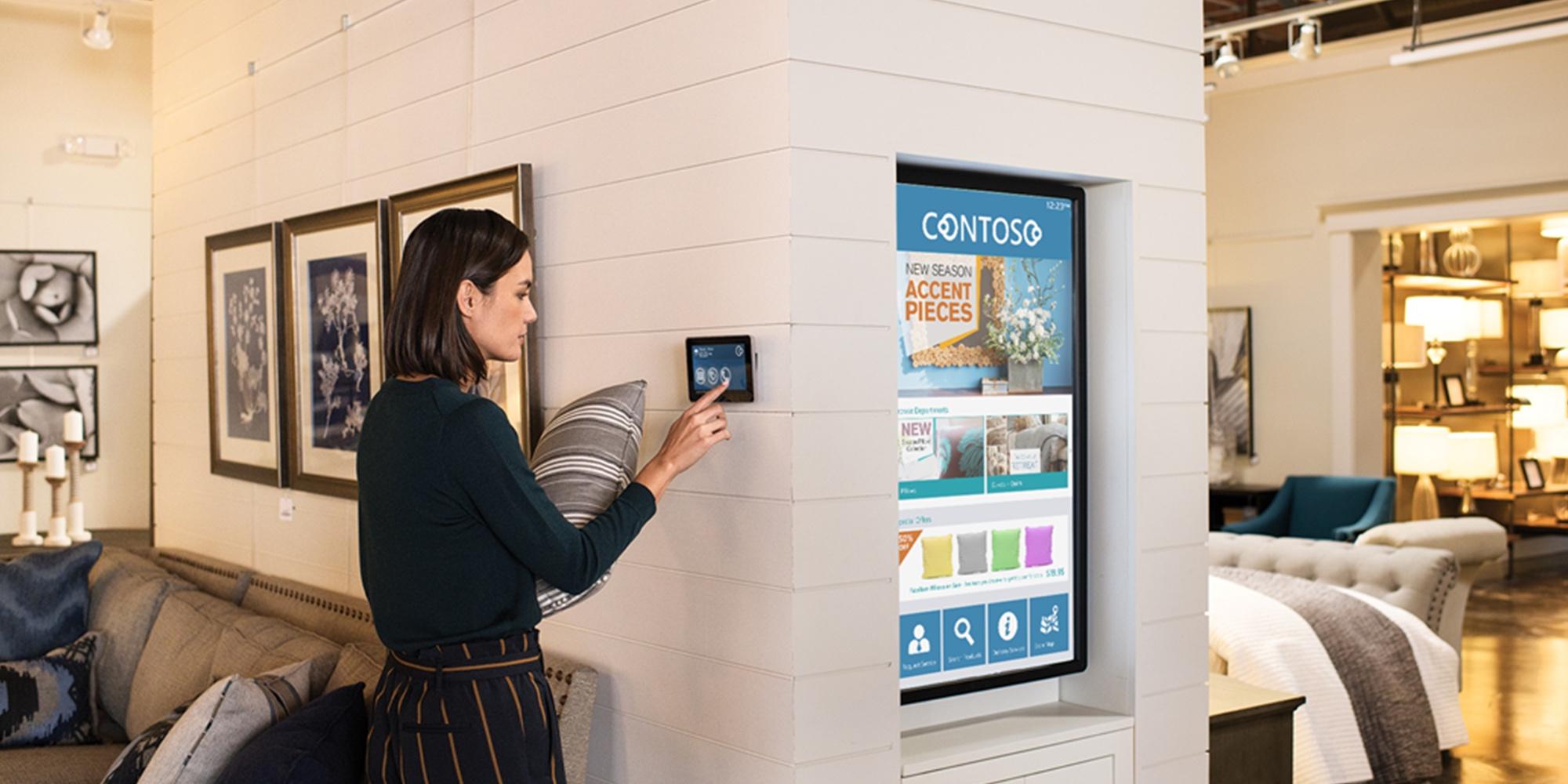 uma mulher em pé numa loja de mobiliário a segurar numa almofada, a utilizar um tablet que está colocado nas paredes da loja