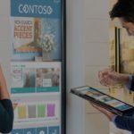een man houdt een tablet vast en een vrouw staat voor een digitaal scherm waarop artikelen van de winkel (kussens) te zien zijn