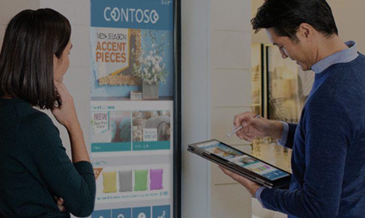 mies pitelee tablettia ja nainen seisoo digitaalisen näytön edessä, näytössä näkyy myymälän tuotteita (tyynyjä)
