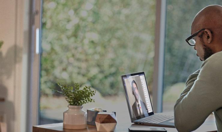 uma pessoa sentada à mesa a utilizar um portátil