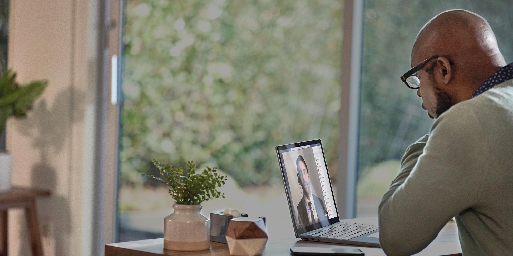 Eine Person, die an einem Tisch sitzt und mit einem Laptop arbeitet