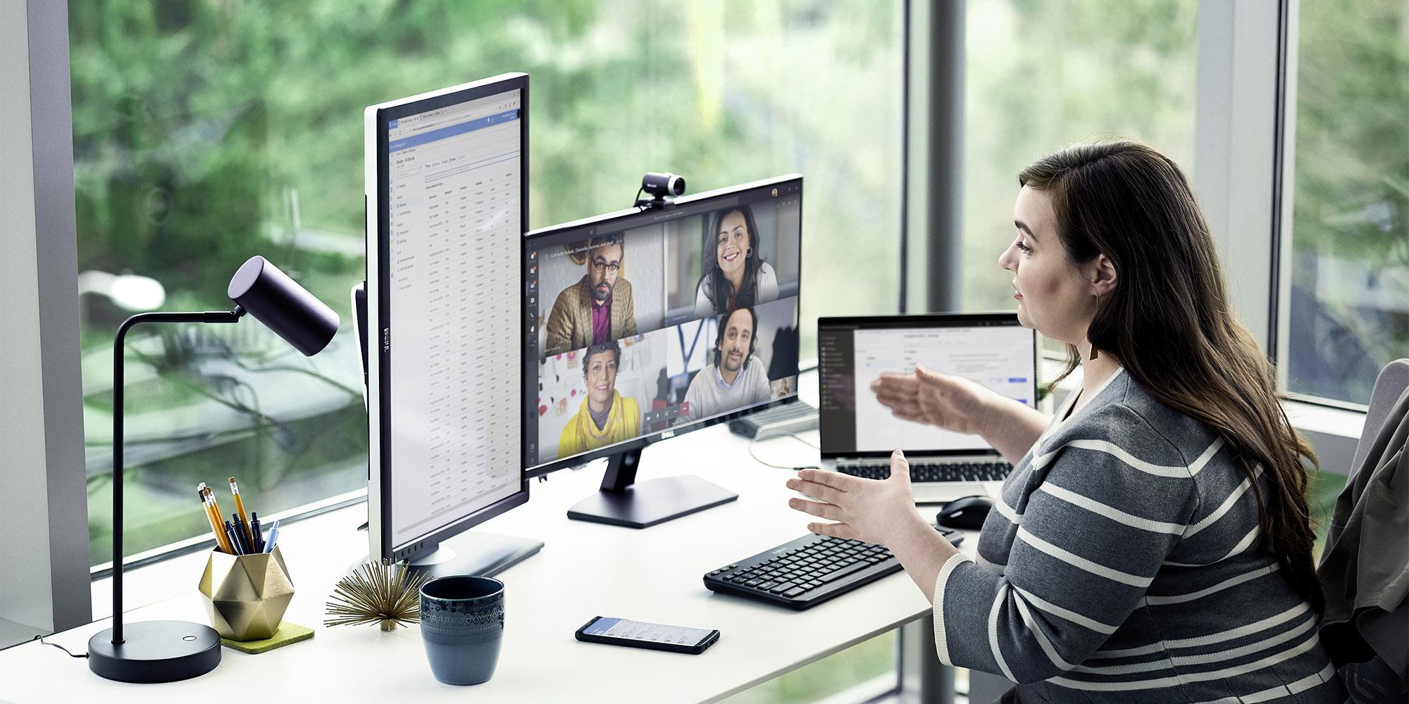 henkilö istuu työpöydällä olevan kannettavan tietokoneen ääressä