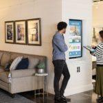 Trabajadores de primera línea femeninos y masculinos de pie en una tienda, frente a un monitor instalado en la pared. Ella está utilizando un portátil convertible Acer (abierto como una tableta) para navegar por las imágenes en un monitor que muestra anuncios de muebles para el hogar.