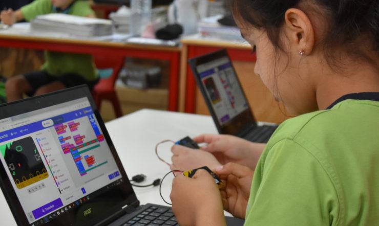 um rapaz jovem a utilizar um computador portátil