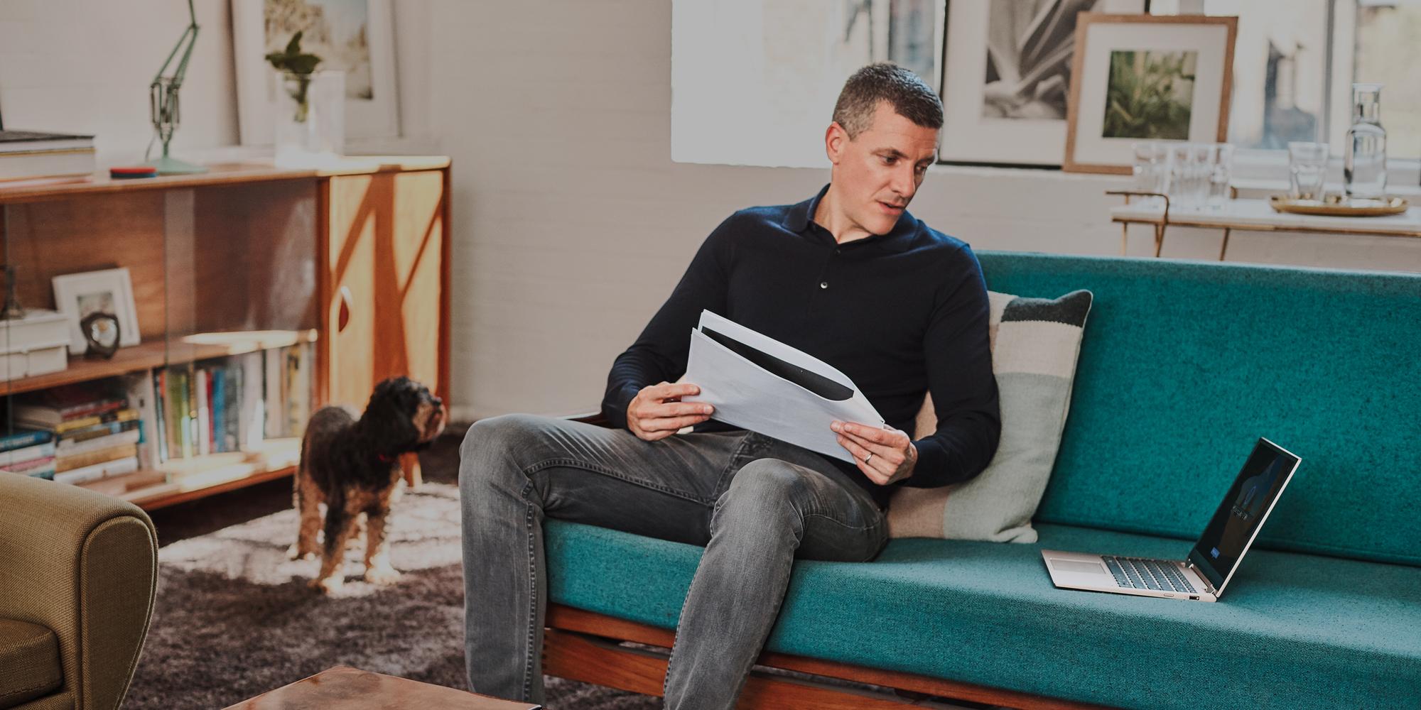 En person sidder i en sofa med sin laptop