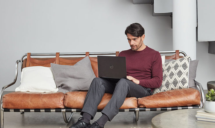 a person sitting on a sofa using a laptop