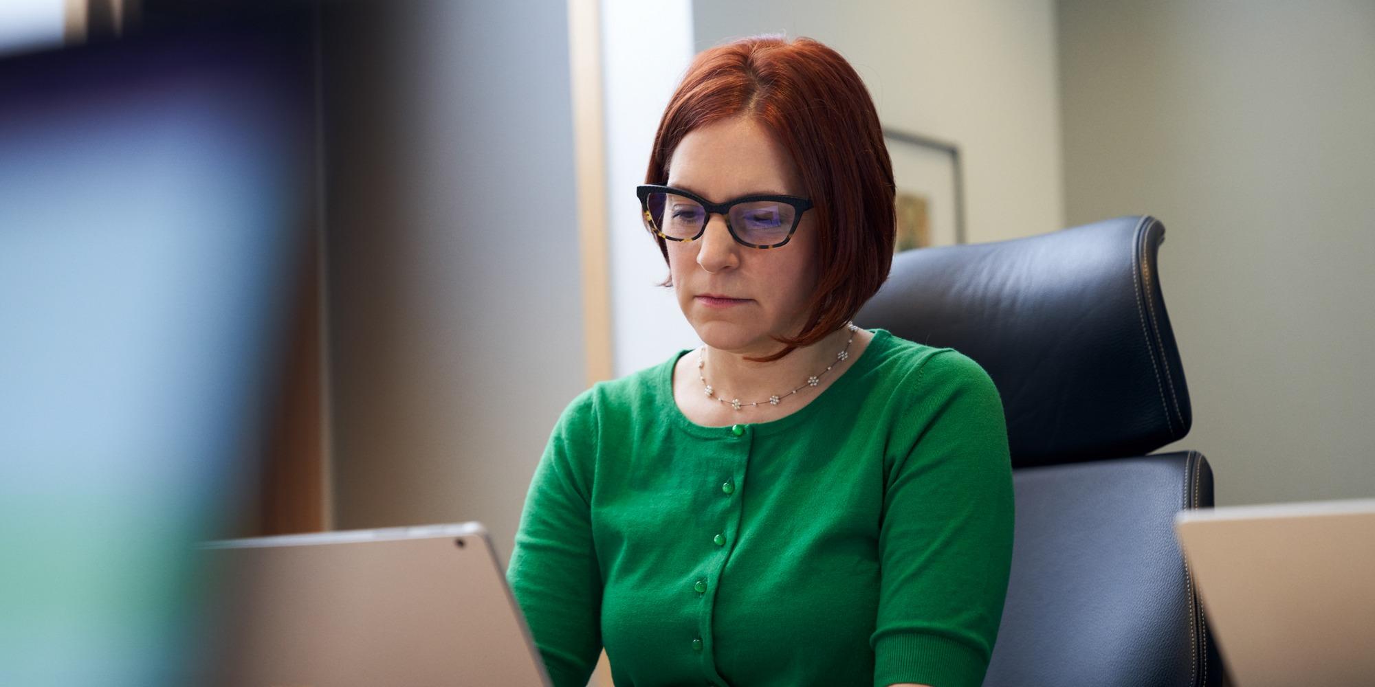 an einem Tisch sitzende und einen Laptop-Computer nutzende Frau