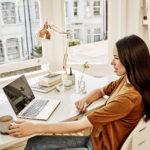 en kvinna som sitter vid ett bord och använder en bärbar dator