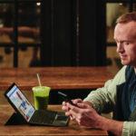 en mand sidder ved et bord og bruger en laptop