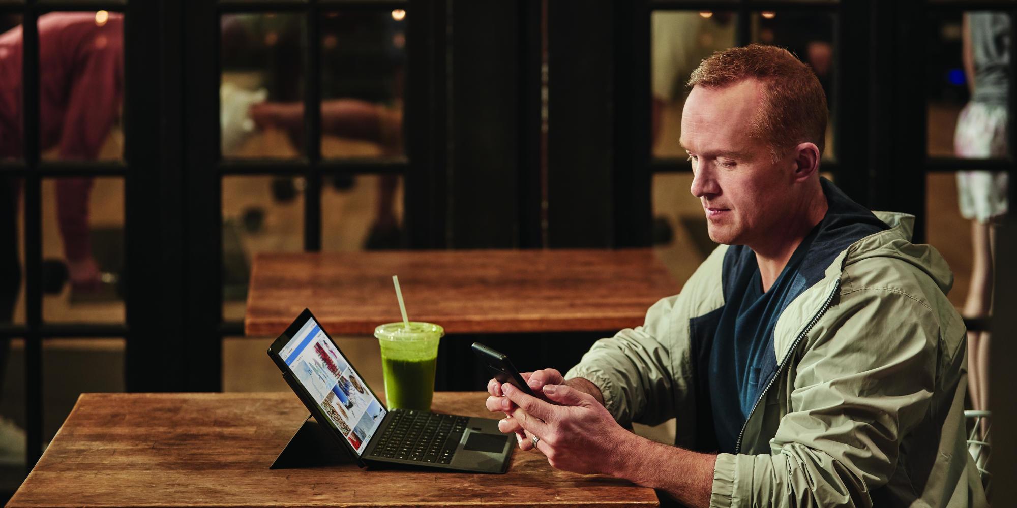 ein Mann, der an einem Tisch sitzt und einen Laptop benutzt