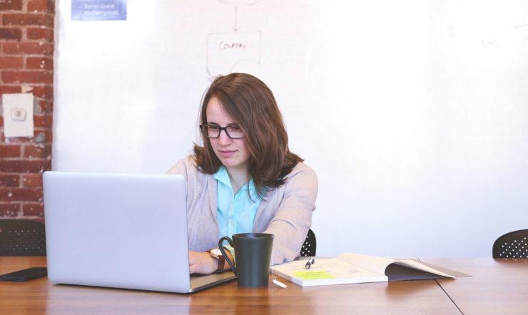 een vrouw zit aan een tafel en gebruikt een laptop