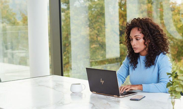 una mujer sentada en una mesa usando un portátil