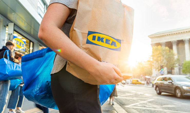a person walking down a street with an Ikea bag