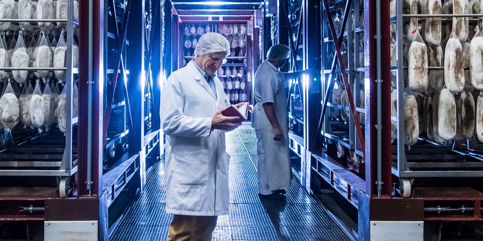 Ein Mann, der vor einem Industriekühlschrank für Lebensmittel steht