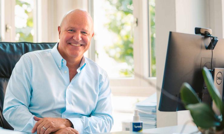 Un homme assis souriant à la caméra