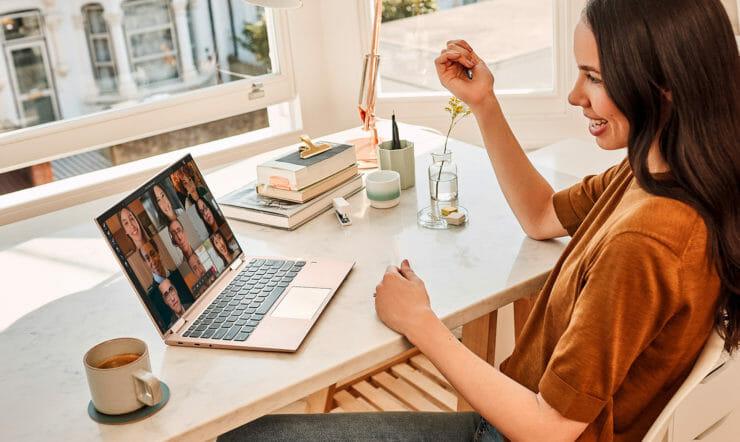 una donna seduta a un tavolo davanti a un computer portatile