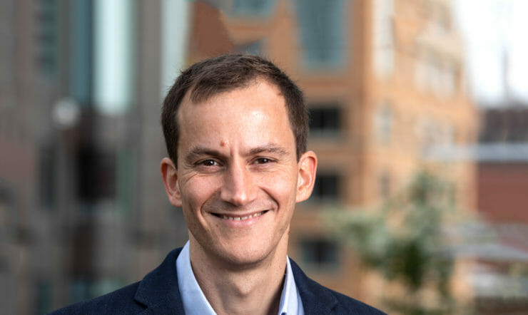 een man in een pak met stropdas lacht naar de camera