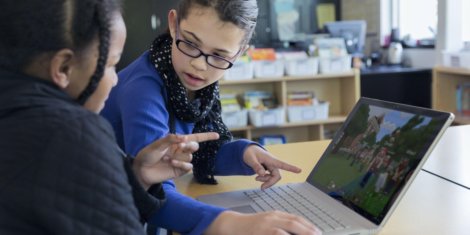 2 meninas a jogar Minecraft à frente de um portátil